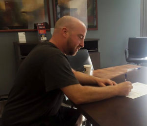 Man signing to purchase a new home in the brokers office.