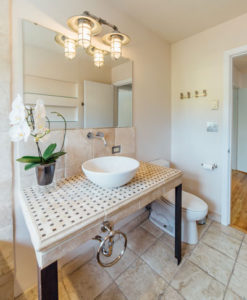 Tiled bathroom with orchid in home for sale by Shayna Denny