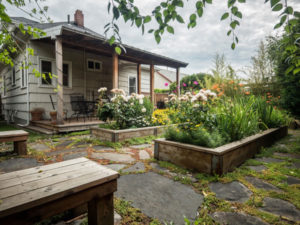 Exterior of home showing raised garden beds and flowers in home for sale by Realtor Shayna Denny