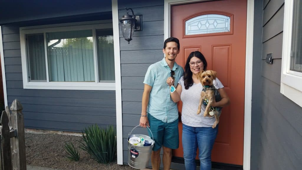 happy homebuyers standing in front of their new home