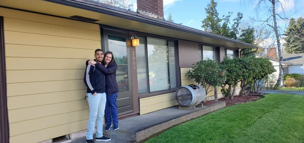 Nick and Jen in front of their new home.